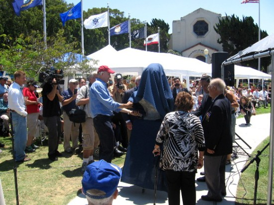 A bust to be set near B-24 Liberator is unveiled by the artist and others.