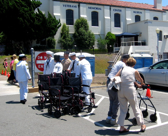 Sailors help the aging American heroes back to their cars.
