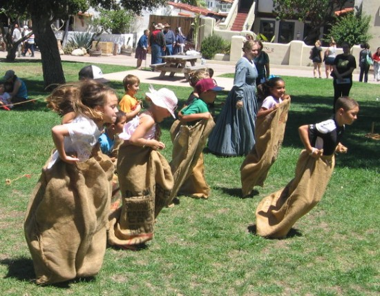 Excited kids blast off across the grass in an old-fashioned sack race!