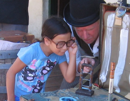 Girl uses magnifying lenses to watch a flea take a swan dive from high platform.
