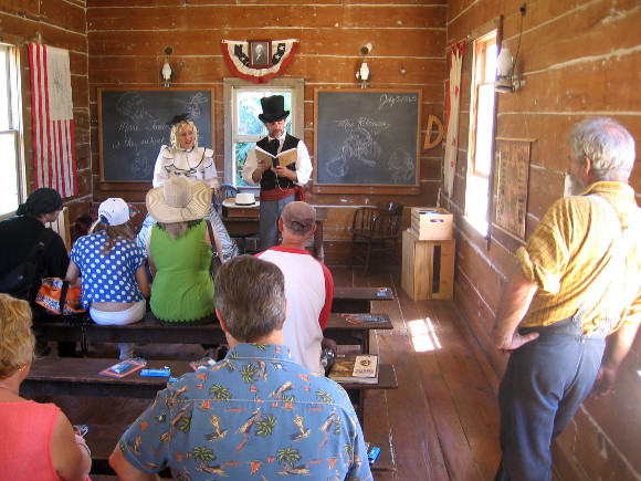 Actors read poetry from Alice in Wonderland in one room schoolhouse.