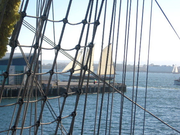 San Diego's tall ship America can be seen on the bay through the rigging.