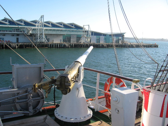 A ship's gun points out past the Broadway Pier.