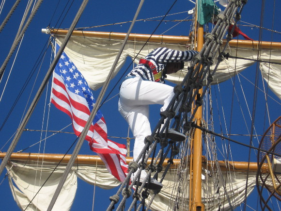 A sailor descends as American flag flies from the visiting vessel.