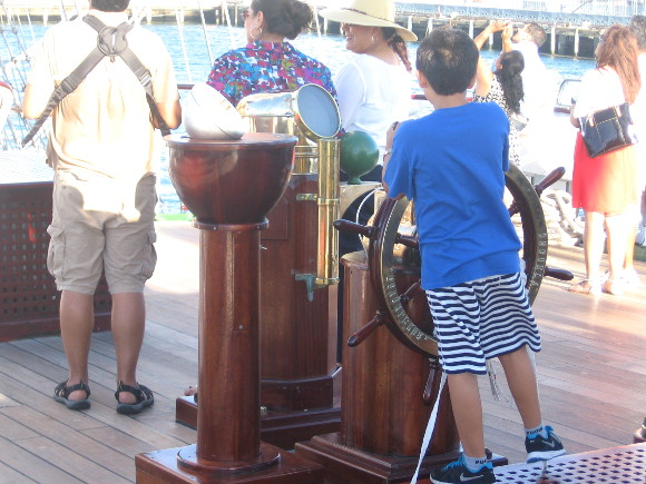A boy pretends to command the sailing ship at the wooden captain's wheel.
