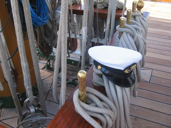 An officer's cap rests atop ropes at one mast's base.