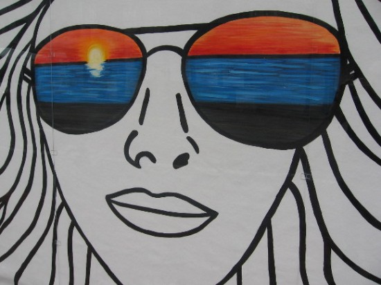 California girl in cool sunglasses watches a sunset.