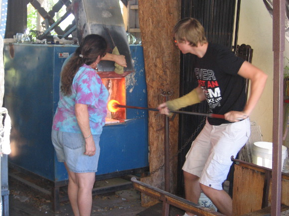 Glassblowers in Spanish Village remove red hot molten glass from furnace.