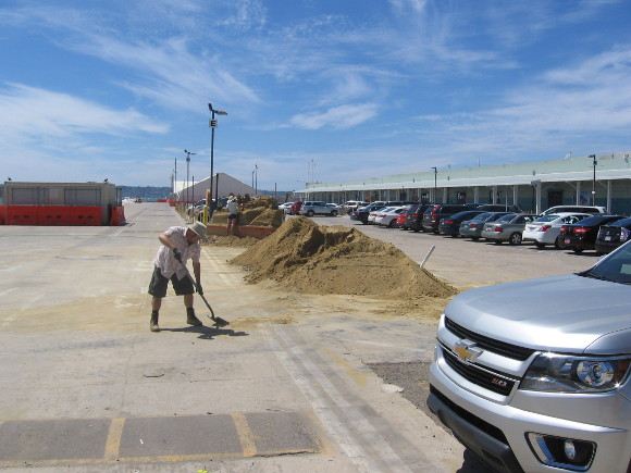 Man shovels spilled sand on pier into one of many big piles.