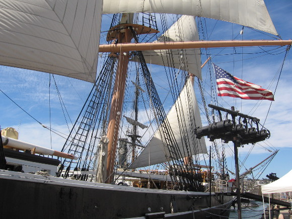 American flag flutters in the breeze at stern of the historic old ship.