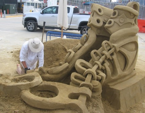Kirk Rademaker works on his shoe sand sculpture on San Diego's B Street Pier.