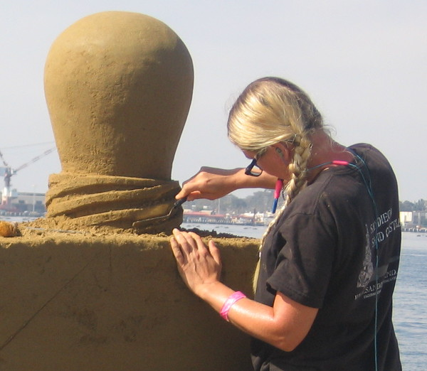 A close look at an artist sculpting with great care.
