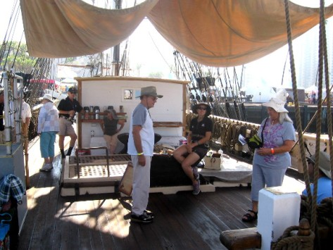 In the shade of a canvas sail, people from the Ocean Institute and visitors chat.