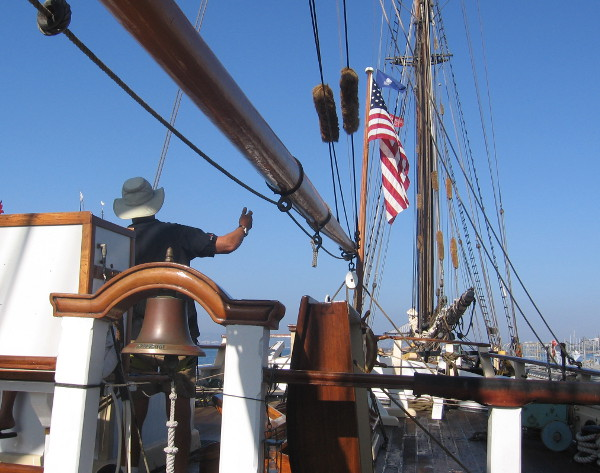 Gazing toward the bow past ship's bell and American flag.