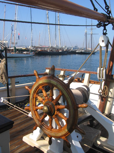 Beyond ship's wheel, several tall ships are docked at Maritime Museum.