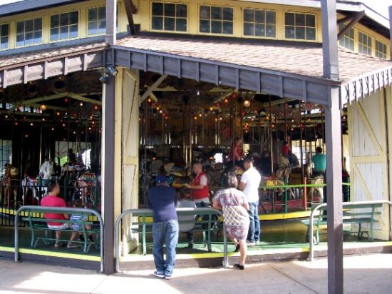 People gaze at the 1910 Herschell-Spillman carousel on a summer day.