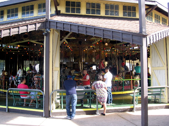 People gaze at the 1910 Herschell-Spillman carousel on a summer day.