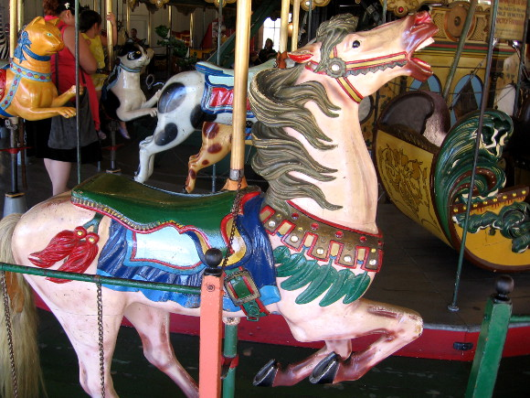 A brightly painted carved wooden horse awaits a passenger.