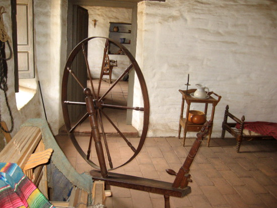 A spinning wheel in one of the simple rooms suggests what life was like.