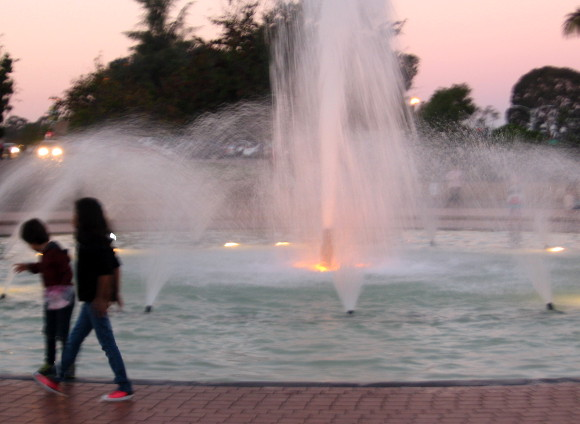 Children walk around Balboa Park fountain as evening descends.