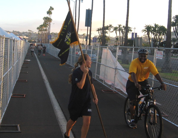 Navy sailors run along Harbor Drive before the Labor Day weekend event begins.