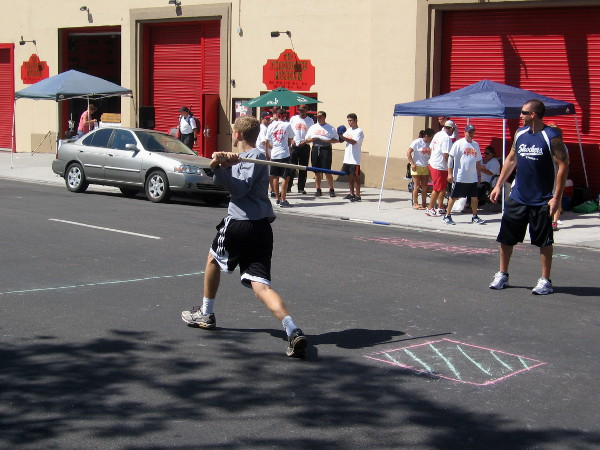 Stickball action in front of the San Diego Firehouse Museum.