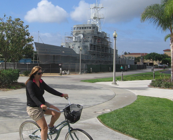 A bicyclist passing the USS Recruit heads into Liberty Station.