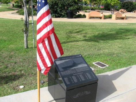 American flag shelters one of the solemn black marble markers.