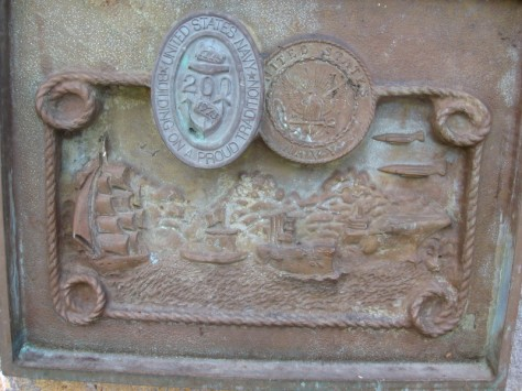 Corroded plaque shows tallship, ironclad, early warship, aircraft carrier and jets.
