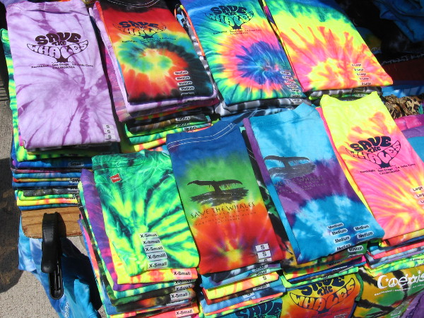 Bright piles of tie-dye shirts for sale on Embarcadero sidewalk.