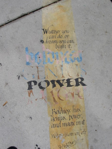 Graphic on sidewalk in front of old library tells of dreams, boldness and genius.