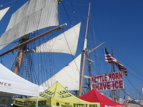 The sails of the historic Star of India rise beyond a kettle corn sign!
