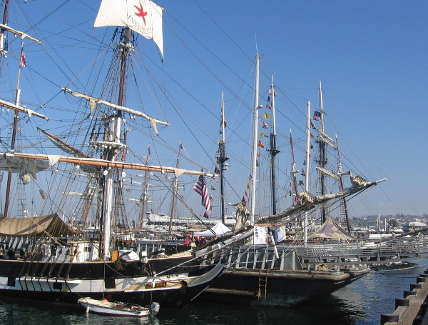 Three temporary floating docks are surrounded by visiting tall ships.