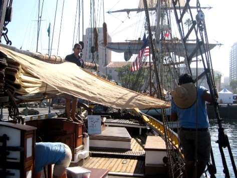 Crew members make adjustments to a canvas sail.