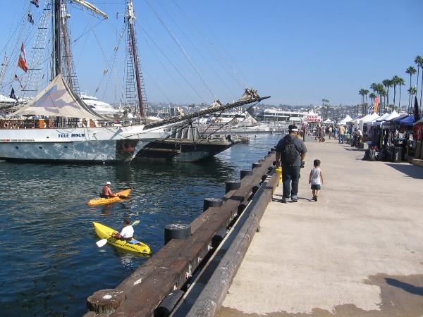 Man and boy walk along Embarcadero at San Diego's 2014 Festival of Sail.