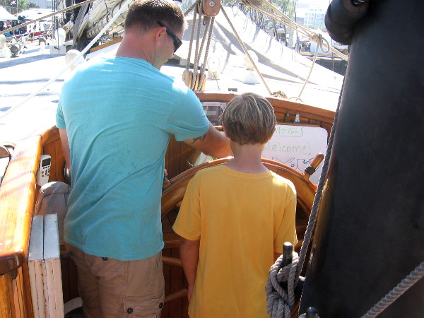 Two generations, side by side, man the helm topside.