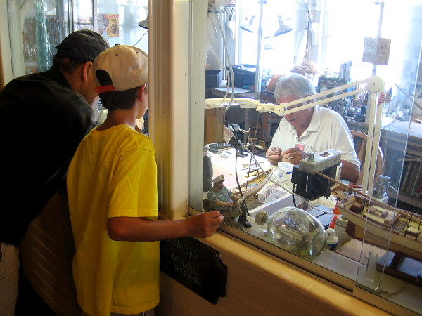 Inside the Berkeley a family watches a hobbyist create a tiny ship model.