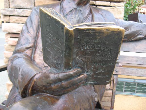 Mark Twain is reading his own classic American novel Adventures of Huckleberry Finn.