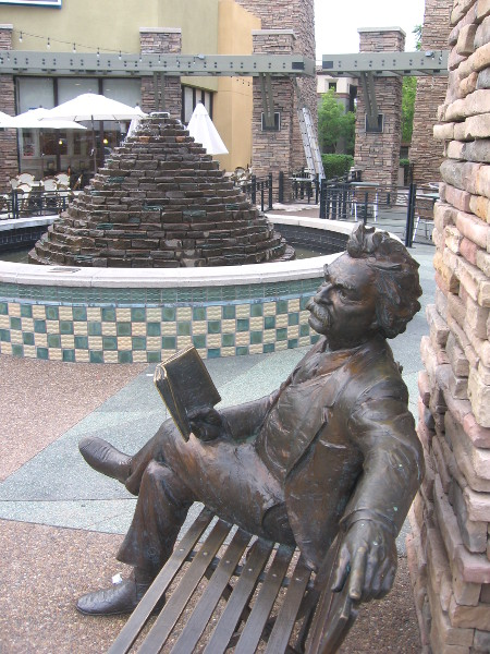 Famous author sits on bench by fountain in front of IHOP.