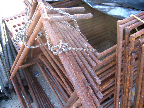 A pleasing pile of rusted metal frames of some sort.