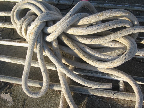 White rope curled softly atop parallel shining rods of metal.
