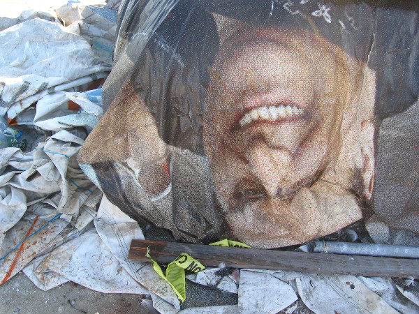 Faded image of a face on a protective tarp smiles upside down.