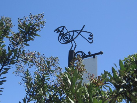 Metal artwork resembles a bird perched atop trees in the downtown community.