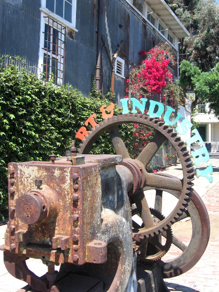 Rusted factory gears on sidewalk with words Art and Industry.