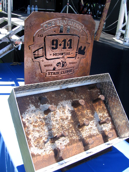 A piece of the fallen World Trade Center on display by stage.