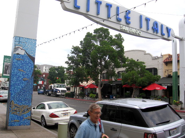 Pedestrian passes Little Italy sign on India Street in San Diego.