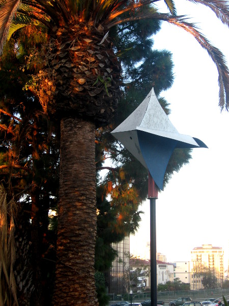 Stylish birdhouse, palm tree and downtown buildings.