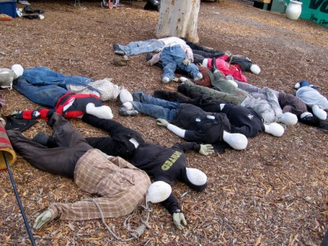 Mangled cloth mannequins lie lifeless on dead leaves.