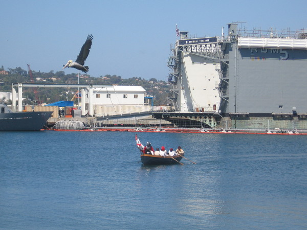 Here comes the row boat containing explorer Cabrillo, a priest and crew members.