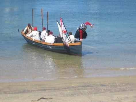 Cabrillo leaps from the galleon's small boat onto the shore!